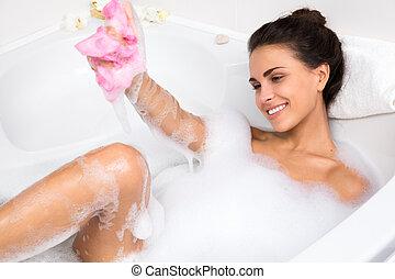 young woman takes bubble bath