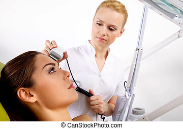 woman having a stimulating facial treatment from a therapist...