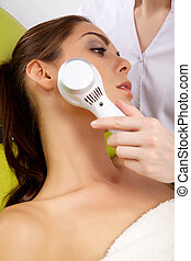 Young woman receiving laser therapy - Young brunette woman...