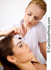 young woman getting beauty skin mask treatment on her face...