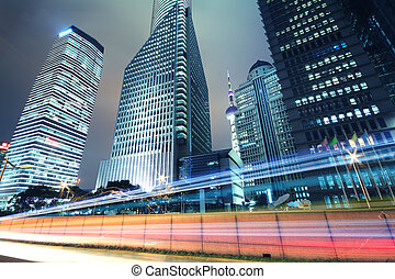 The City background of modern office buildings car night light trails in Shanghai