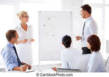 business team working with flip chart in office - smiling...