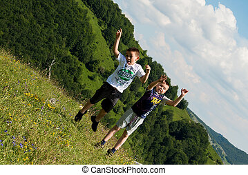 kids jumping in meadow