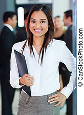 young indian office worker holding a clipboard