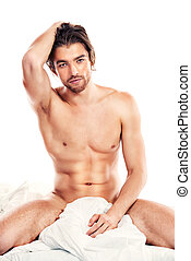 seducer - Handsome nude man sitting on a bed. Isolated over...