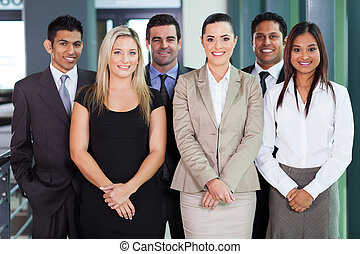 group of young businesspeople standing together in office