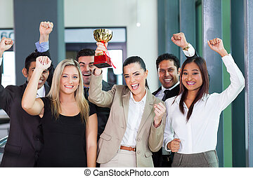 cheerful business team winning an award for their...