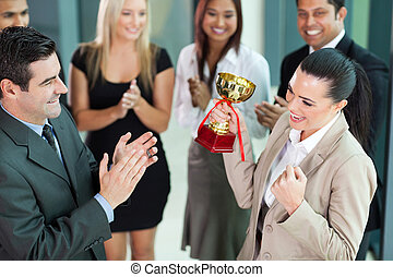 cheerful female corporate worker receiving a trophy -...