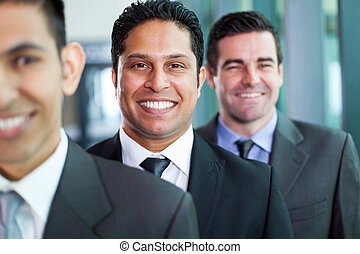 businessmen standing in a row - three smiling businessmen...