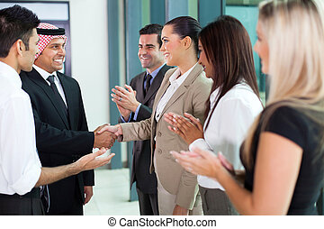 young translator introducing arab businessman to group of...