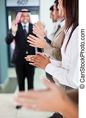 business team applauding to welcome arabian businessman