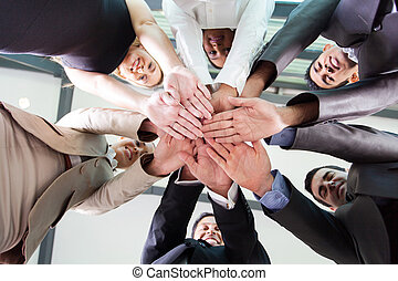 underneath view of business people hands together