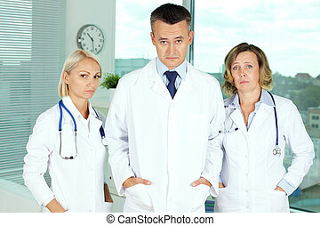 Pessimistic doctors - Portrait of three uniformed doctors...