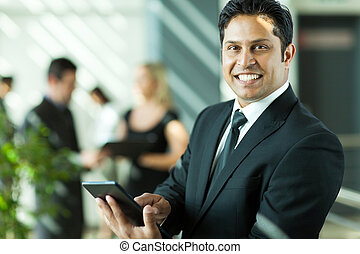young indian businessman working on tablet computer
