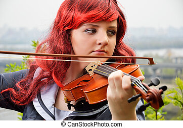 Close-up of teenage girl playing the violin outdoors