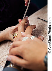 nail spa - close-up image of a pare of jeweled fingers being...