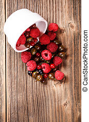 Mixed berries scattered on vintage wooden table