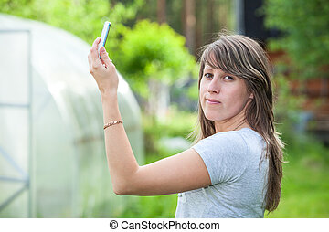 Yuong Caucasian woman holding phone up and looking at camera