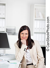 Businesswoman sitting at her desk in the office
