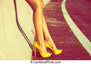 tan legs - woman tan legs in high heel yellow shoes outdoor...