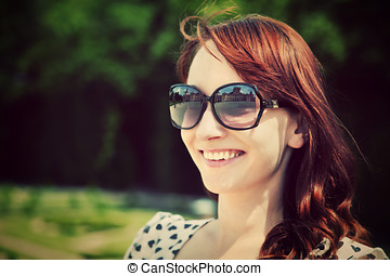 Young beautiful woman in sunglasses smiling in a summer park.