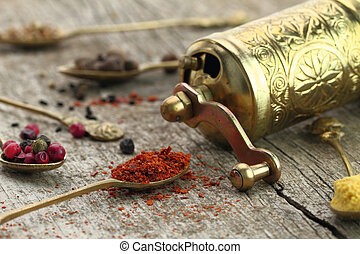 Old spoons with spices and pepper grinder on wooden...
