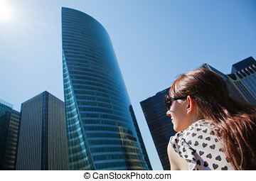 Young woman looking up at the business skyscrapers, sunny...