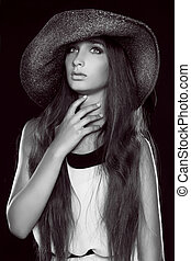 Fashion portrait of beautiful  woman posing in hat, black and white photo
