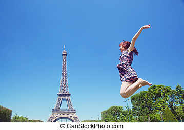 Young attractive jumping against Eiffel Tower, Paris, France...