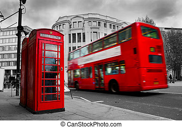 London, the UK. Red phone booth and red bus in motion....
