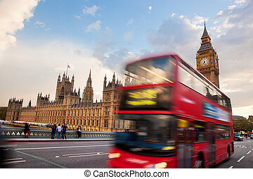 London, the UK. Red bus in motion and Big Ben, the Palace of...