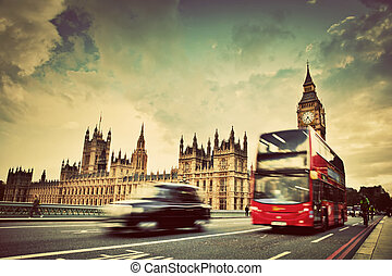 London, the UK. Red bus, taxi cab in motion and Big Ben, the...