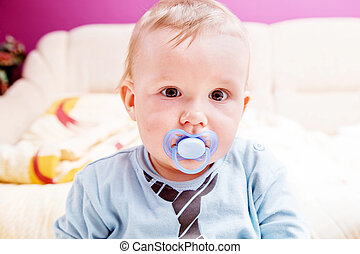 Young baby boy with a dummy in his mouth portrait - Young...