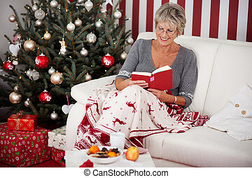 Senior lady reading in front of the Christmas tree - Elderly...