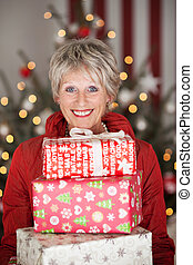 Happy senior with Christmas gifts - Happy smiling beautiful...
