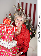 Smiling senior lady with a pile of Christmas gifts