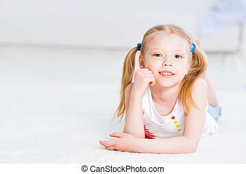 close-up portrait of a cute girl, lying on the floor in the...