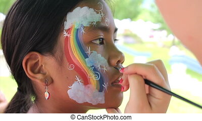 Girl Gets Rainbow Face Painting - A cute 11 year old Asian...