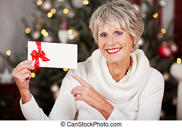 Smiling woman pointing to a Christmas voucher - Smiling...
