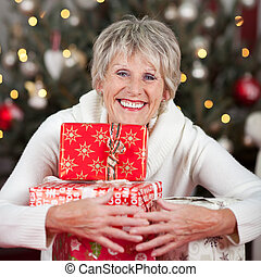 Laughing woman hugging a pile of Christmas gifts - Laughing...