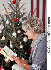 Senior lady reading in front of the Christmas tree - Stylish...