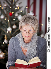 Elderly lady reading a book at Christmas