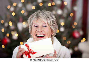 Laughing elderly lady with an Xmas gift voucher holding the...