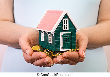 House on a pile of money in woman hands - House on a pile of...