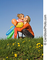 Girl kissing her mother - Cute girl with balloons kissing...
