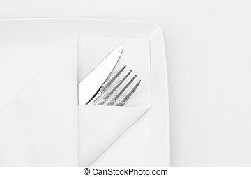 Place setting, white plate with cutlery and white napkin