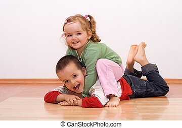 Happy brother and sister playing wrestling on the floor