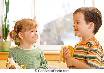 Two kids eating bananas