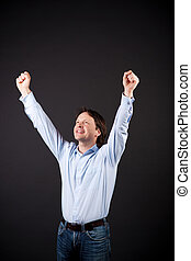 Young man rejoicing raising his fists to the air in...
