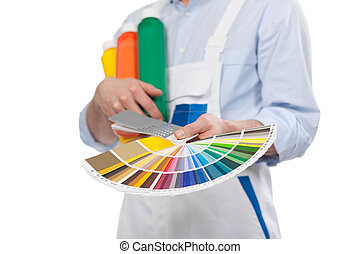 Handyman with paint colour cards in the colours of the...